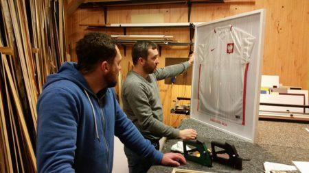 Właściciele Ramy w Bramie patrzą na swoje dzieło - oprawioną koszulkę Arkadiusza Milika