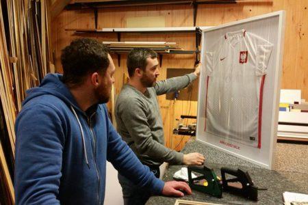 Marcin i Łukasz rzucają ostatnie spojrzenia na swoje wspólne dzieło. Oprawiona koszulka polskiej reprezentacji.
