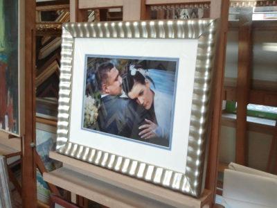Fotografia ślubna pokryta szkłem w falowanej, ozdobnej, pozłacanej ramie.