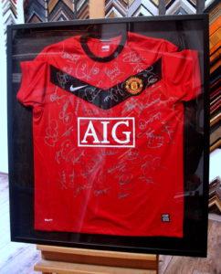 Czerwona koszulka Manchester United z autografami w ciemnej gablocie.