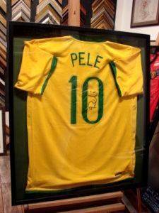 Brazylijska koszulka piłkarska Pele z autografem w ciemnej gablocie.