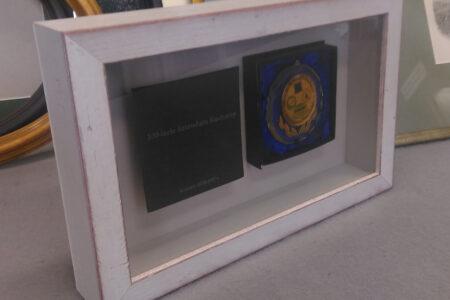 Pamiątka 100-lecie Sztandaru Kucharzy. Zawartość zamknięta za szkłem UV. W drewnianej ramie malowanej na biało.
