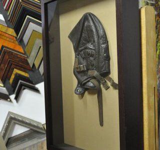 Czapka pilota. Umieszczona w drewnianej ramie. Bladożółte passe-partout. Za szkłem muzealnym.