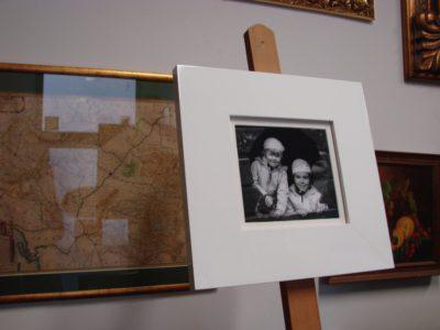 Dzieci. Kontrast pomiędzy czarno-białą fotografią a białą ramą. Drobne zdjęcie zachowane w szerokim, białym obramowaniu.