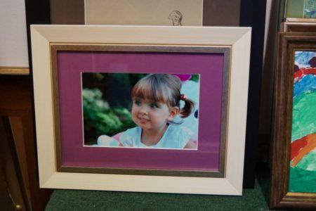 Fotografia dziecka z różowym passe-partout za szkłem w jasnej ramie.