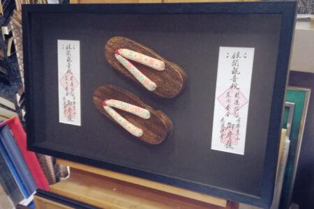 Drewniane japonki w czarnej ramie za szkłem UV UltraVue